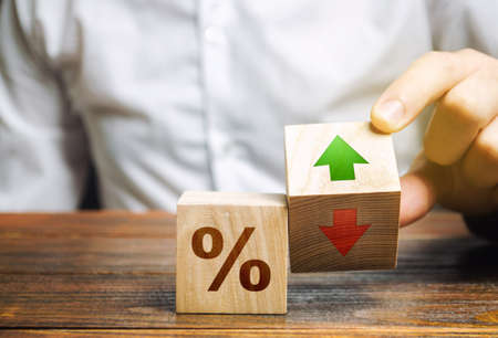 Businessman holds wooden blocks with percent and up or down arrow. Mortgage and loan rates. Interest rate, stocks, ranking. Business and finance concept. Stock Photo