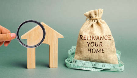 Money bag with the words Refinance your home and miniature house. Real estate concept. Business and finance. Mortgage, loan. Interest rates. Home Lending Standard-Bild