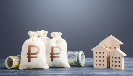 Russian ruble money bags and residential buildings figures. Investments in real estate. Municipal budget management. Taxes. Mortgage loan. Financing the construction and renovation of housing.