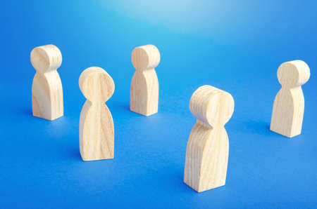 Wooden figurines of people stand on a blue background. Loneliness and disconnection. Safe spacing between persons, new normal. Faceless mass. Communication. Society public. Disunity concept. Stockfoto