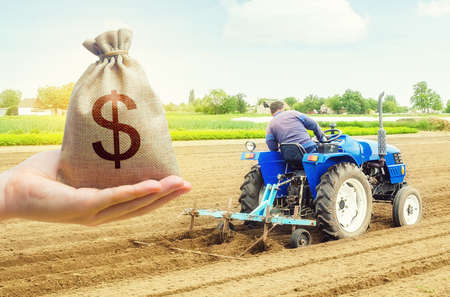 A hand holds out a dollar money bag on a background of farmer on a tractor making mounds rows on a farm field. Lending farmers for purchase land and seed, modernization. Support subsidies. Farm loans