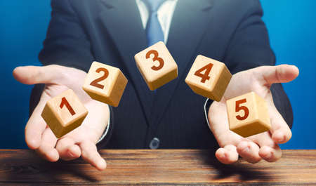 Man throws 5 numbered blocks with the numbers one two three four five from his hands. Five easy steps. Organization and systematization, step by instructions. Business planning, action plan. Reklamní fotografie