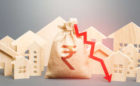 City residential buildings and indian rupee money bag with a red down arrow. Low cost of real estate. Falling prices for rental apartments. Low demand for home buying. Lower mortgage interest rates. Reklamní fotografie