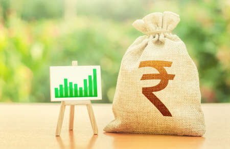 Indian rupee money bag and easel with green positive growth graph. Economic development. Business sentiment. High deposits profitability. Recovery and growth of economy, good investment attractiveness 免版税图像