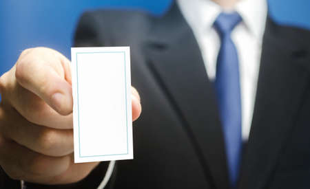 Businessman introduces himself with a vertical business card. Presentation, hands over contacts to client. Business advertising. Attracting new customers. Agent offers his services. Solidity and style