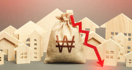 City residential buildings and south korean won money bag with a red down arrow. Low demand for home buying. Lower mortgage interest rates. Falling prices for rental apartments. Low cost real estate. Standard-Bild