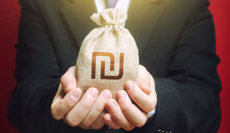 Man holds out a Israeli shekel money bag. Budget management, collect taxes. Bank issuance of credit and loans to business. Insurance payout. Financial crisis support, benefits, subsidies. 免版税图像