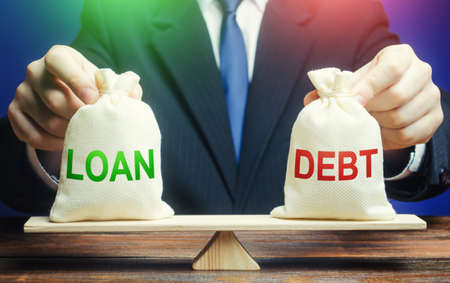 A businessman holds bags with a loan and debt on scales. Financial system balance difficulties. Borrow loans to pay off debts load, debt restructuring. Avoiding default bankruptcy, business support. 免版税图像
