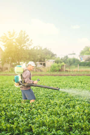 A farmer with a mist sprayer spray treats the potato plantation from pests and fungus infection. Harvest processing. Protection and care. Agriculture and agribusiness. Use chemicals in agriculture.