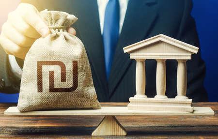 Businessman puts a israeli shekel money bag on scales opposite to government state building. Financing Social programs. Payment of taxes and fees. Lending to government projects. Bank deposit