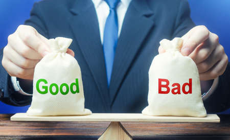 Businessman holds good and bad bags on scales. Evaluating the actions of other people, weighing the positive and negative qualities. Good and evil, karma. Introspection. Ethics and acceptability.