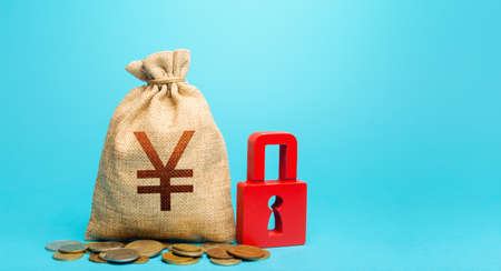 Yen Yuan money bag and red padlock. Blocking bank accounts and seizing assets. Tight government control over the financial system. Freezing of pension savings. Cash flow monitoring.