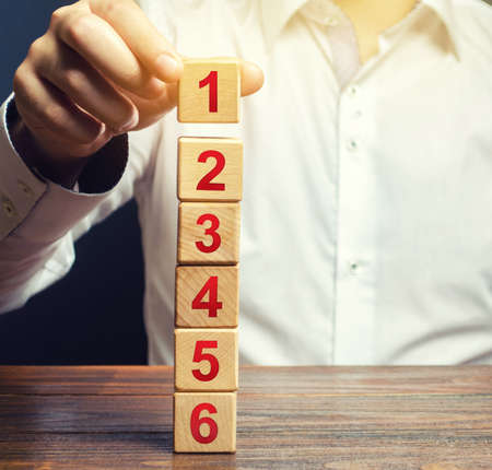 The man builds a tower of the sides of the numbers. Simple steps for execution. Organization and systematization, instructions. Business planning, action plan. Planning and tactics, alternate solution Banque d'images