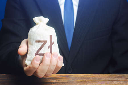 A businessman holds in his hand a polish zloty money bag. Stimulating economic recovery. Investments, financing. Providing business with preferential loans and support during the economic crisis.