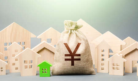 Yen Yuan money bag and a city of house figures. Buying real estate, fair price. City municipal budget. Development and renovation of buildings. Investments. Cost of living in town. Property tax.
