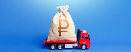 Truck is carrying a huge russian ruble money bag. Anti-crisis measures of government. Great investment. Attracting large funds to the economy for subsidies, support and cheap soft loans for businesses 版權商用圖片