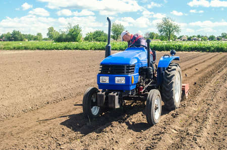 Farmer on a tractor loosens the soil with milling equipment. Loosening surface, land cultivation. Farming, agriculture. Plowing field. Use of agricultural machinery and to simplify and speed up work.