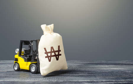 Forklift transports a south korean won money bag. Crisis recovery measures. Attraction of investments in business and economy, cheap loans, leasing. Borrowing on capital market. Stimulating economy.