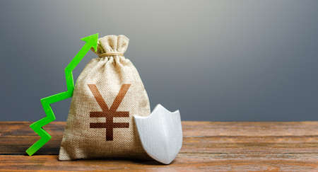 Yen Yuan money bag with a shield and a green arrow up. Safety security of investments, financial system stability. Increasing maximum amount of guaranteed deposits insurance compensation. Stok Fotoğraf
