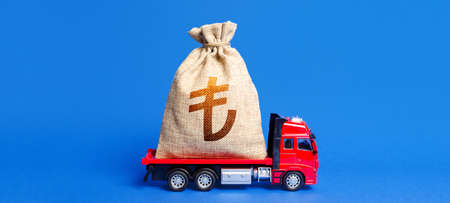Truck is carrying a huge turkish lira money bag. Anti-crisis measures of government. Attracting large funds to the economy for subsidies, support and cheap soft loans for businesses. Great investment.