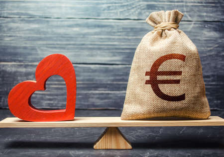 Euro money bag and red heart on scales. Health life insurance financing concept. Subsidies. Funding healthcare system. Reforming and preparing for new challenges. Support and life quality improvement Stok Fotoğraf
