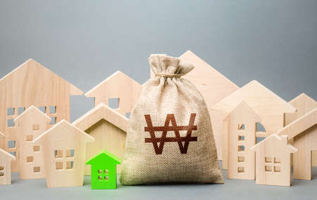 South korean won money bag and a city of house figures. City municipal budget. Buying real estate, fair price. Investments. Cost of living. Property tax. Development, renovation of buildings.