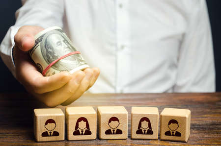 A man holds out money dollars over blocks with employees. Fair pay increase. Incentives for employees with bonuses. Investments. Company personnel costs maintenance. Payday. Salaried workers.