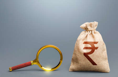 Indian rupee money bag and magnifying glass. Find high-paying job. Most favorable conditions for deposits, loans. Origin of capital and legality of funds. Search for financing. Financial audit.