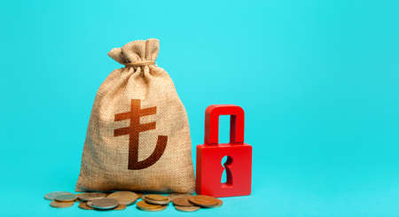 Turkish lira money bag and red padlock. Blocking bank accounts and seizing assets. Freezing of pension savings. Tight government control over the financial system. Cash flow monitoring.