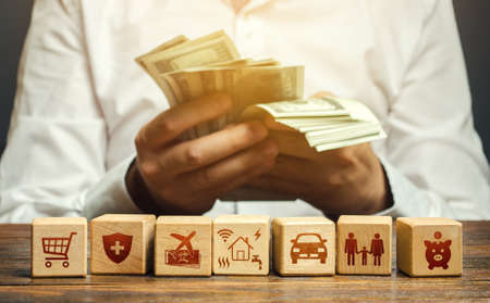 A man counts money and blocks with the attributes of family needs. Family budget concept, bills expenses, vacation and transportation. Optimal salary, sustain an acceptable standard of living. Stok Fotoğraf