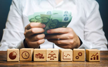 A man is counting money and blocks with business attributes. Good business model. Profitability. The rules for successful investment. High performance, great work. Company management Stock Photo