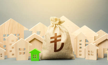 Turkish lira money bag and a city of house figures. Investments. City municipal budget. Buying real estate, fair price.Cost of living. Property tax. Development, renovation of buildings. Stock Photo