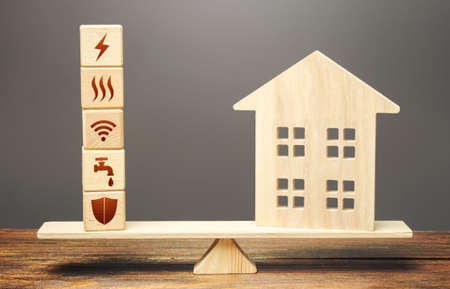 House and blocks with utilities public service symbols on scales. Availability of bill payment. Home is too big and its maintenance costs are high. Improve water and energy efficiency. Energy saving Stock Photo