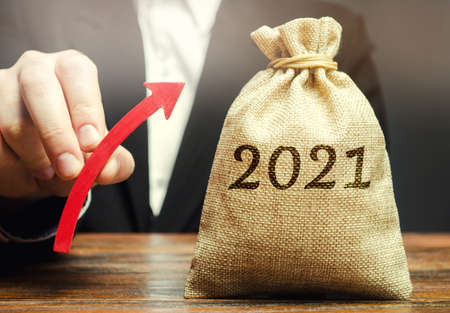 Businessman holds an up arrow near the 2021 money bag. Strategy and budget planning. Vision. Business forecasting. Growth and development of business and economic. Goals and plans. Investment. Stock Photo
