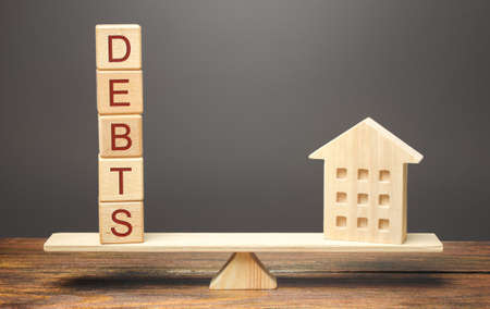 Wooden blocks with the word Debts and a miniature house on the scales. The concept of paying off debts for real estate and housing. Mortgage, loan. Rent apartment Standard-Bild