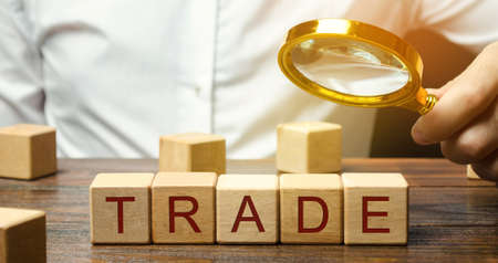 Businessman holds a magnifying glass over the word Trade. Business market and finance concept. Transfer of goods or services. Money, economy. Business deal. Trading on the stock exchange