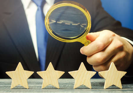 A man holds a magnifying glass over four stars. The evaluation of visitors. Quality level, good service. Best customer rating. Feedback. Rating of hotels and restaurants. Selective focus