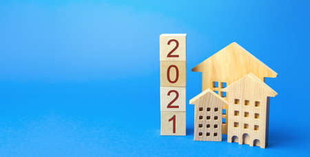 2021 wooden blocks and miniature house. Real estate concept. Family budget planning. Investments, plans, savings. Mortgage and mortgage rates. Forecasts. Loan. Refinance home Stock Photo