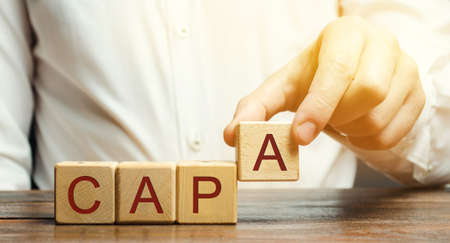 Businessman puts wooden blocks with the word CAPA. Corrective and Preventive action plans. Business management concept. Strategy and efficiency. Improving organizational processes. Performance