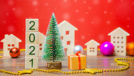 Wooden blocks 2021, Christmas tree, miniature houses and gifts. New Year or Xmas winter holiday. Decoration, celebration. The concept of the beginning of the new year. Snowfall