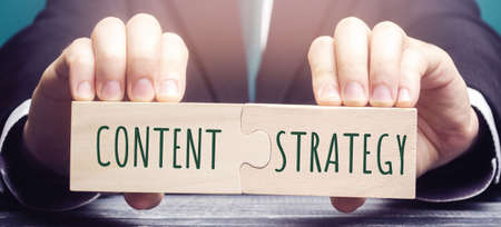 Businessman puts together wooden puzzles with the words Content strategy. Planning, development, and management of content concept. Create measure research promote publish optimize. Web development Stock Photo