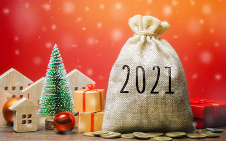 Money bag 2021, Christmas tree, miniature houses and gifts. New Year or Xmas winter holiday. Accumulating money and planning a budget. Business and finance. Loans, deposit, credit. Promotions, offers