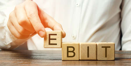 Businessman puts wooden blocks with word Ebit - earnings before interest and taxes. Measure of a firm's profit that includes all incomes and expenses. Operating income. Business and finance concept