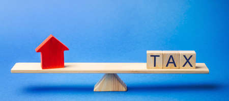 Wooden blocks with the word Tax and a house on scales. The concept of paying taxes on real estate and housing. Debt repayment. Mortgage, loan, credit. Apartment and apartments