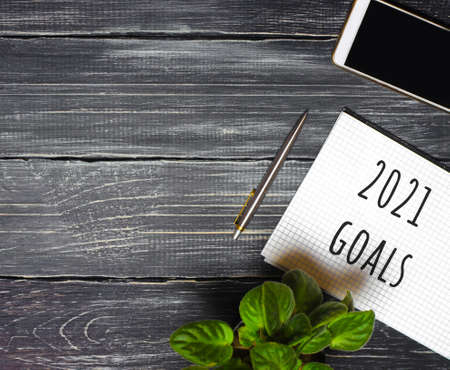 2021 Goals concept. Desktop with notebook, phone, pen. Motivation, inspiration. Planning, plans and tasks. New business ideas. Setting goal, target.