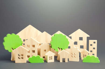 City of figures houses and green trees. Real estate concept. Urbanism and infrastructure. Realtor services. Infrastructure. Affordable housing. City greening. Effective town management.