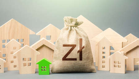 Polish zloty money bag and a city of house figures. Investments. City municipal budget. Property tax. Development, renovation of buildings. Buying real estate, fair price. Cost of living. Stock Photo