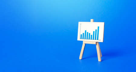 An easel with a positive growth chart. Minimalism. Concept of business growth, development, achieving success and successfully confronting crisis challenges. Increase economic indicators. Education. Stock Photo