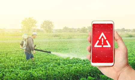 Phone in hand displaying a warning against background of a farmer with a mist sprayer fogger on a farm field. Use of dangerous chemicals for the treatment of plants and crops. Potential health hazard. Stock Photo