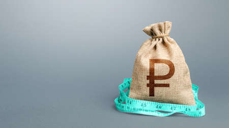 Russian ruble sterling money bag and measuring tape meter. Analysis of economic situation. Assessment of capital. Declaration of income, illegal. Formation and optimization of the budget, savings. Stock Photo